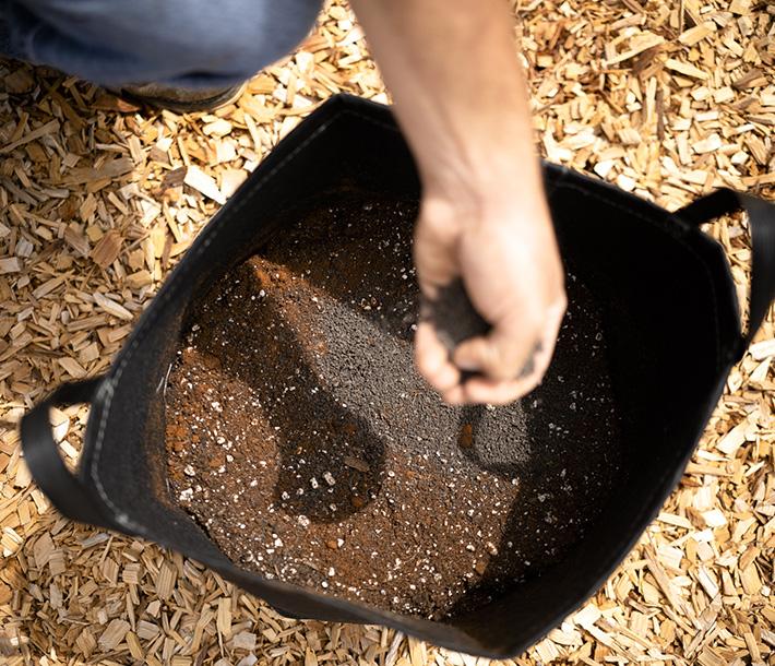A gardener mixes Geoflora VEG into soil inside a GeoPot Fabric Pot with handles
